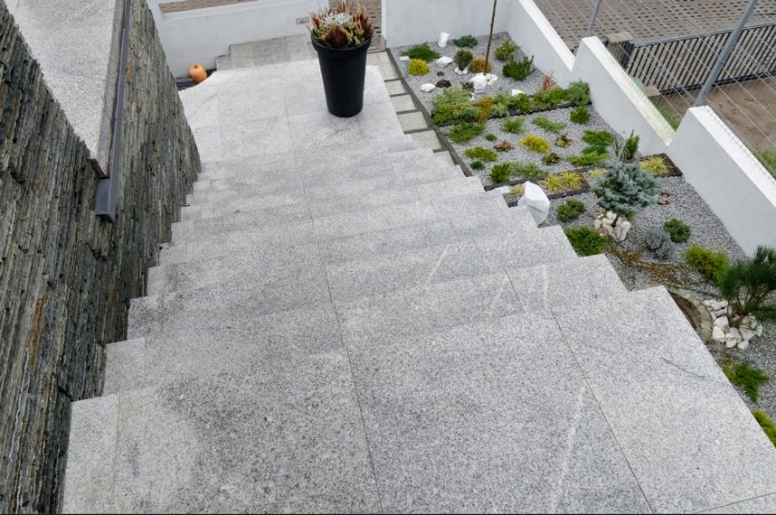 Kamień na elewacji dobrze komponujący się ze schodami i ogrodem z kamienia