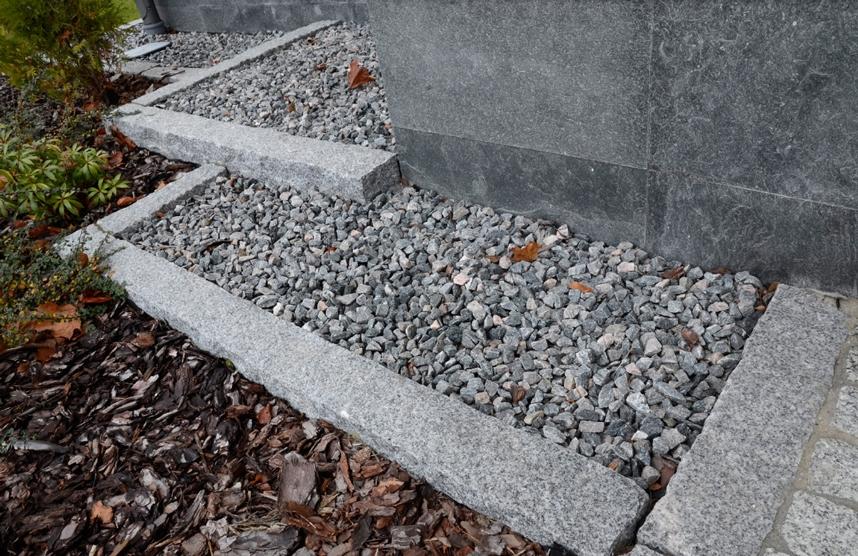 Płyty na elewacji budynku obsypane kamyczkami w obrzezach granitowych